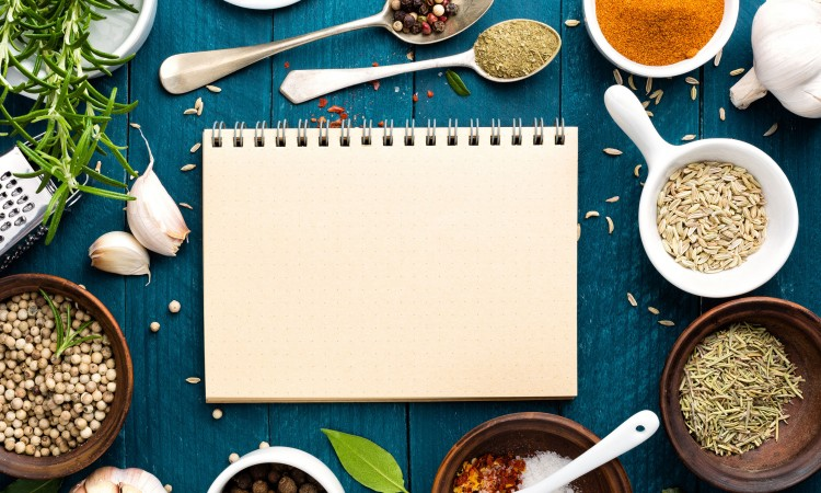 53694353 - culinary background and recipe book with various spices on wooden table